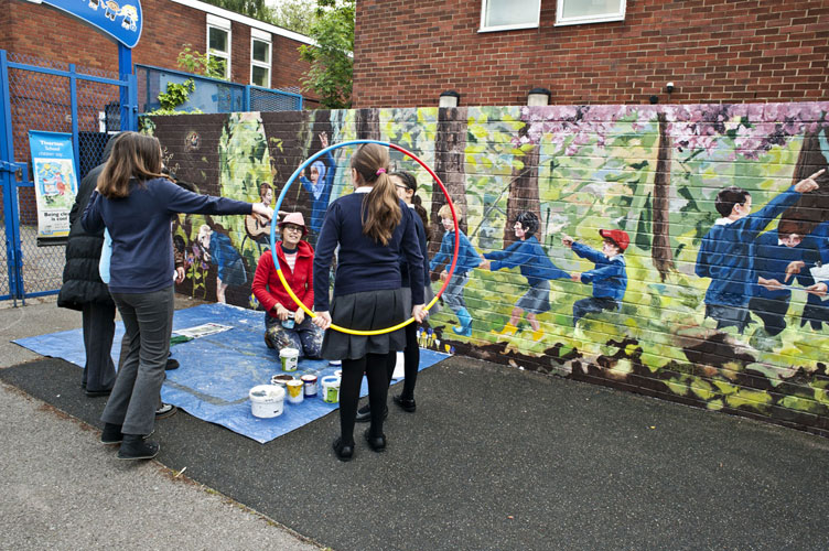 school kids watch mural artist